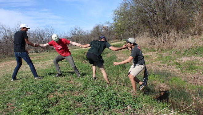 """Abilene Christian University environmental science class students """"studied"""" the outdoors last weekend, helping clean Cedar Creek. The students were Jacob Chapman of Andrews, Justin Mendoza of Abilene and Bill Ramage and Jacob Hutchison, both of Dallas. The effort sometimes required teamwork to get up slippery, sloping banks."""