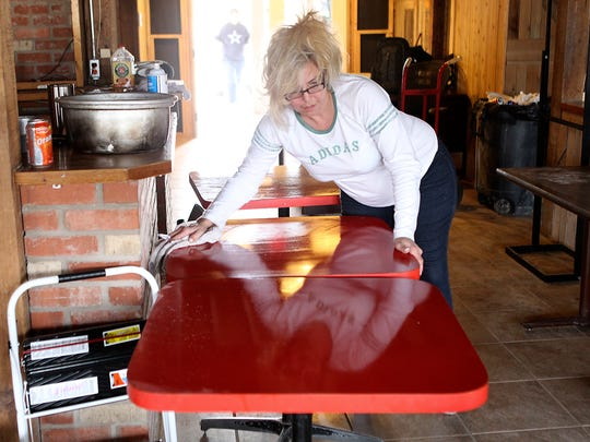 A member of the San Angelo Clubhouse wipes down tabletops