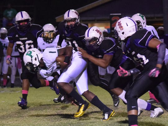 Peabody quarterback Talon Bowens (1) gains a few yards while under pressure from Marksville defenders Thursday.