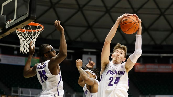 Portland forward Jacob Tryon grabs a rebound over Houston during the second half of the NCAA college basketball game Sunday, Dec. 22, 2019, in Honolulu. (AP Photo/Marco Garcia)