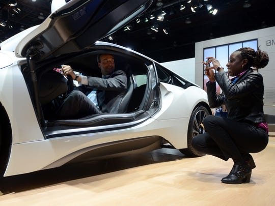 Event goers snap photos in a BMW Tuesday, Jan. 12, during the North American International Auto Show at Cobo Hall.