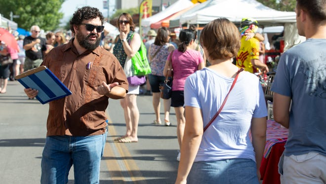 Lucas Herndon, voter registration agent, walks along the Las Cruces Farmers and Crafts Market on Saturday, July 21, 2018, asking those who pass by him if they would like to register to vote. Herndon was protesting the Farmers Market request that voter registration agents need to stay in place. Market officials have since changed their position.