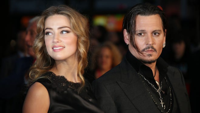 """Amber Heard, left, and Johnny Depp arrive at the premiere of Depp's film """"Black Mass,"""" at the London film festival."""
