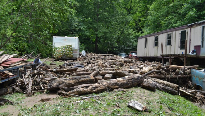 Logs washed up against a home after a mud slide and flash flood linked to a Pike County surface mine.
