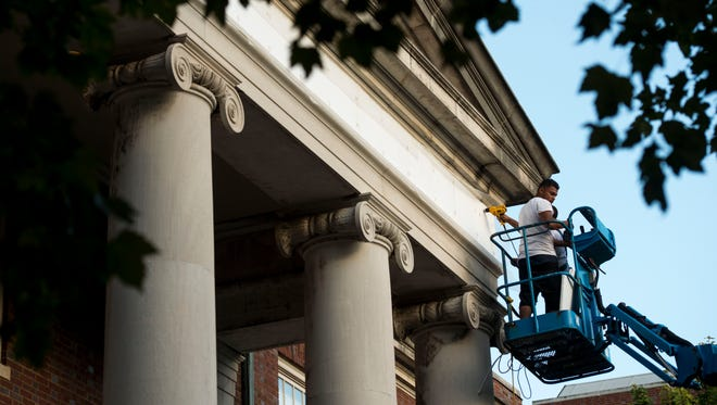 Workers cover up the name on the exterior of Confederate Memorial Hall at Vanderbilt University on Monday, Aug. 15, 2016. Vanderbilt will repay an 83-year-old donation, allowing it to remove the Confederate name from the residence hall.
