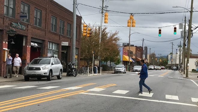 A pedestrian crosses Haywood Road in a marked crosswalk Saturday afternoon. The APD does conduct enforcement operations on crosswalks, but motorists tend to follow the law when a marked car is there, APD says.