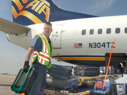 4/29/03 Slug: ata30 Assign: 83554 Star staff photo by Rob Goebel-INDIANAPOLIS-This is a photo for biz of refueling of an ATA jet at the Indianapolis International Airport today. IN THIS PHOTO:   Baggage handler Dale Burggett unloads luggage from  an arriving ATA plane this afternoon.
