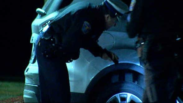 Police inspect an SUV after a driver said some shot at her vehicle early Tuesday near I-275 in Forest Park.