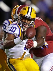 LSU quarterback Anthony Jennings (10) pitches a lateral to avoid a sack in the Crimson Tide's 20-13 win in overtime Saturday. Jennings threw for 76 yards and a 14-yard touchdown pass to Malachi Dupre.