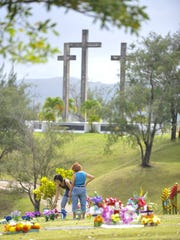 In this file photo, Flo Uson, left, and Trini Lacuata clean and decorate the grave sites of loved ones at the Our Lady of Peace Memorial Gardens.