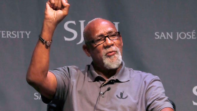 FILE - In this Oct. 17, 2018, file photo, 1968 Olympic athlete John Carlos raises his fist as he speaks about his experience as Olympians who participated in Mexico City in 1968 during the 50th Anniversary of the Defining Moment in Sports Social Activism Historic Town Hall at San Jose State University in San Jose, Calif. Olympic protestor John Carlos co-authored a letter with an influential American athletes' group calling on the IOC to abolish the rule that bans protests at the Olympics and replace it with a policy written in collaboration with athletes. Carlos and Tommie Smith raised their fists on the medals stand at the 1968 Olympics to protest racial inequality in the United States.
