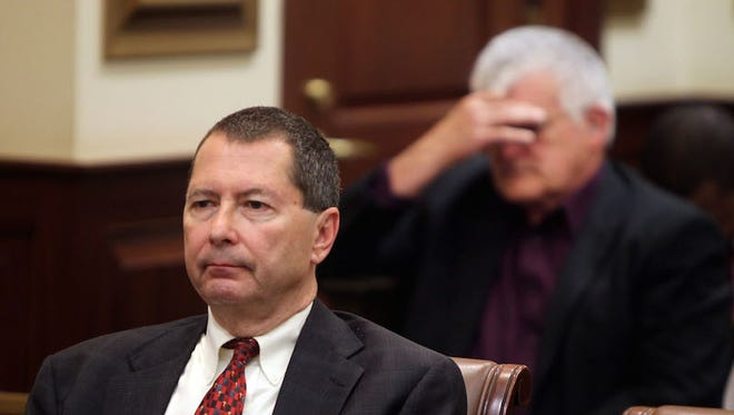 "Former State Rep. Peter Beck (left) sits in court while attorneys confer with Judge John West after Beck was found guilty of 13 offenses, including several counts of perjury. Behind him is Larry Cook, of Monfort Heights, who said he was a ""victim of the Ponzi scheme"" for which Beck was charged.  He said he was happy with West's verdict.  ""I'm tired of being lied to,"" he said, ""This was about greed."""