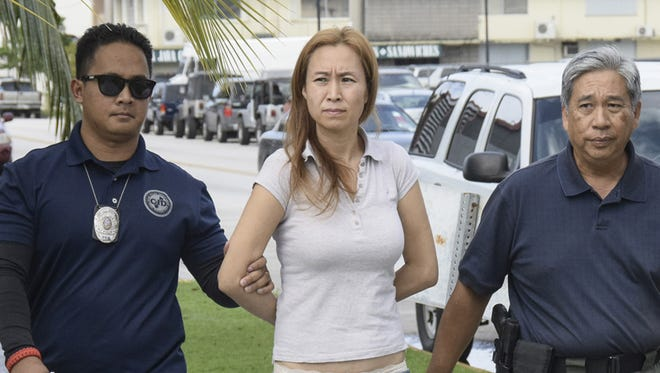Yu Hua Han, 44, of Tamuning, is escorted into the Hagåtña precinct by Guam Police Department detectives on Jan. 2. She was arrested for allegedly punching a 10-month-old baby in the face at the Micronesia Mall on New Year's Day.