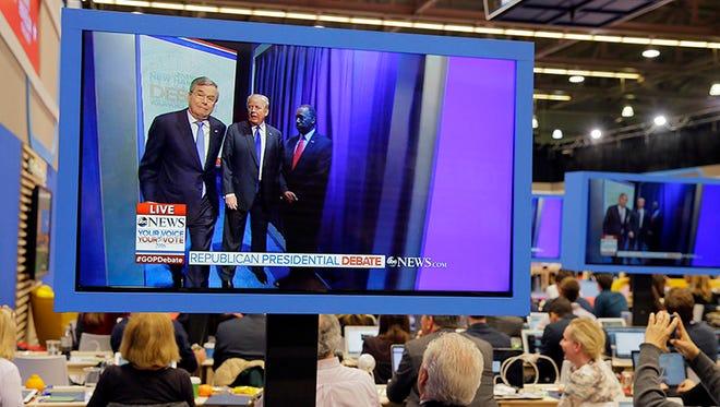 Jeb Bush, Donald Trump and Ben Carson are seen on press room monitors prior to the start of the Feb. 6, 2016, Republican debate.