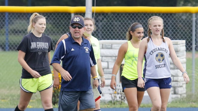 Notre Dame girls soccer head coach Steve Weber leads his team onto the field for practice Aug. 15 at Brewer Memorial Stadium.