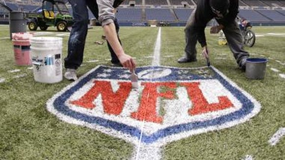 Workers paint an NFL championship logo earlier this year at CenturyLink Field in Seattle.
