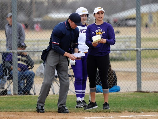 Hardin-Simmons coach Chanin Naudin talks with the home plate umpire to make a change during the Cowgirls' 7-6 loss to McMurry on Tuesday, Feb. 13, 2018.