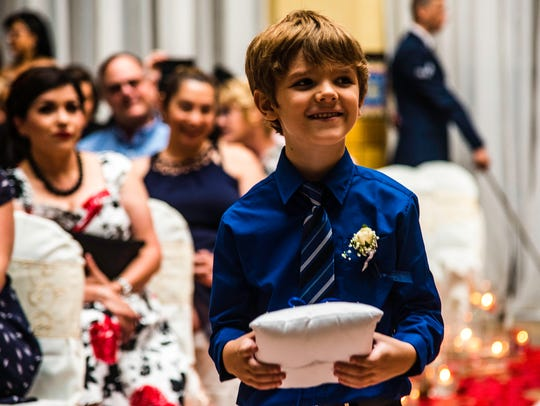 The ringbearer smiles on his way down the isle.