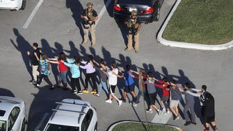 People are brought out of the Marjory Stoneman Douglas High School after a shooting in Parkland, Fla. Feb 14, 2018