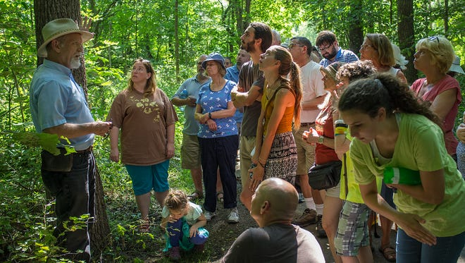 People gather around as Peter Carrington, Assistant Curator at the Beal Botanical Gardens at MSU talks about edible plants Sunday, August 16, 2015.