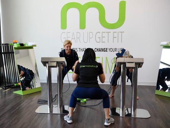 Trainer Amy Sengbouttarath, center, works with Daphne