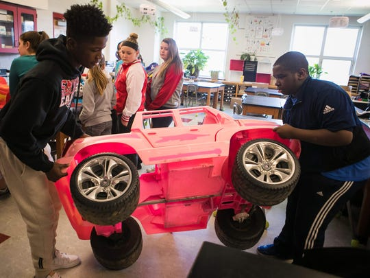 Eighth-graders Devin Demoe (left) and Terence Henry at Smyrna Middle school carry a toy vehicle into the classroom where they are adapting it for children with disabilities.