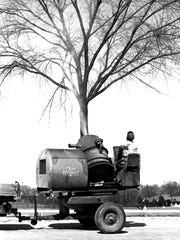 City of Sheboygan maintenance worker spraying American Elm trees with DDT to kill the European elm bark beetle. 1963. Sheboygan Press image.