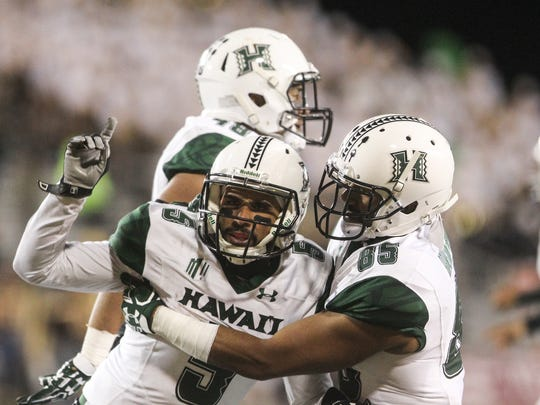 Hawaii wide receiver Marcus Armstrong-Brown (85) embraces wide receiver John Ursua (5) after he scored a touchdown last week against Wyoming. Ursua leads the nation in receiving yards per game.