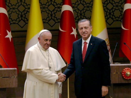 Pope Francis, left, shakes hands with Turkish President