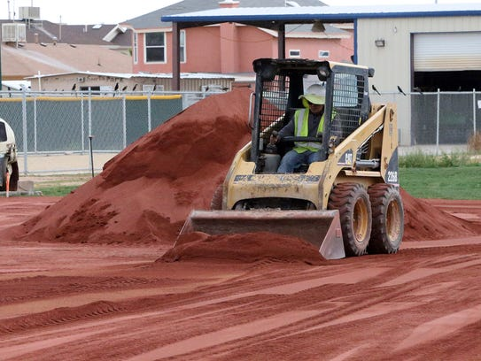 A worker spreads infield clay material onto a baseball