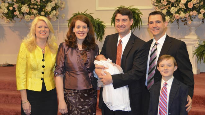 In this 2012 photo provided by a former member of the church, Jeffrey Cooper holds his infant daughter at her 2012 baby dedication at the Word of Faith Fellowship compound in Spindale. At second right is Frank Webster, an assistant North Carolina prosecutor who is married to church leader Jane Whaley's daughter, Robin, left. At right is Frank Webster's son, Brock. At second left is Jeffrey Coopers' wife, Natalie. Frank Webster and Chris Back - church ministers who handle criminal cases as assistant DAs for three nearby counties - provided legal advice, helped at strategy sessions and participated in a mock trial for four congregants charged with harassing a former member, according to former congregants interviewed as part of an AP investigation of Word of Faith.