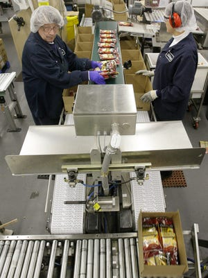 Workers fill boxes with cheese Thursday Jan. 6, 2011 at Sargento.