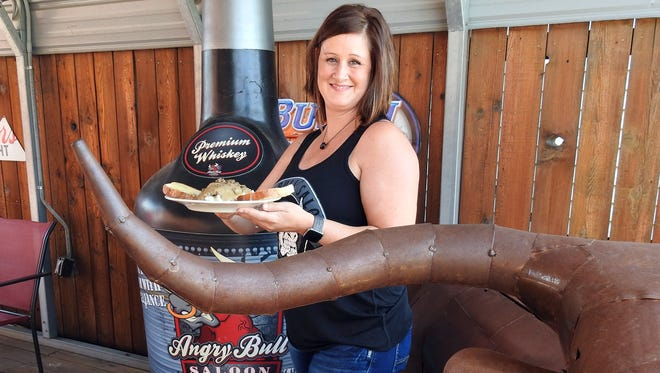 Angry Bull Saloon manager Regan Kinder displays the hamburger gravy on mashed potatoes, the Friday lunch special. The saloon offers several daily lunch and dinner specials throughout the week.