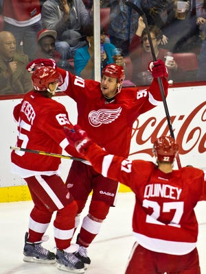 Detroit Red Wings forward Stephen Weiss, middle, celebrates his goal with defenseman Danny DeKeyser, left, and defenseman Kyle Quincey (27), during the second period of an NHL hockey game against the Ottawa Senators in Detroit, Monday, Nov. 24, 2014.