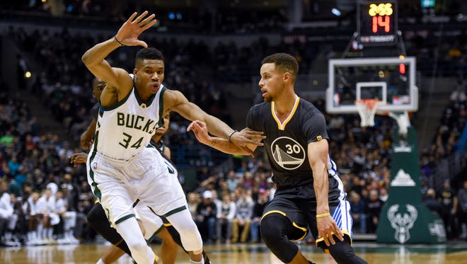 Milwaukee's Giannis Antetokounmpo defends Warriors guard Stephen Curry in the first quarter of the Bucks' 124-121 loss to Golden State on Saturday night at the BMO Harris Bradley Center.