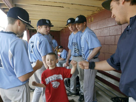 Six-year-old Dayton Frulio gets fist bumps from members of the Mater Dei Prep baseball team at the Strike Out Autism Baseball Challenge at Veterans Park in Berkeley Township in 2014.