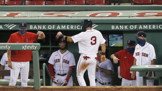 Boston'sJose Peraza (3) celebrates after scoring on a double by J.D. Martinez during the third inning of an opening day baseball game against the Baltimore Orioles at Fenway Park, Friday in Boston.