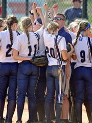 Chambersburg coach Chris Skultety, in blue,  gathers with his undefeated softball team during a 6-1 win over Red Land on Tuesday.