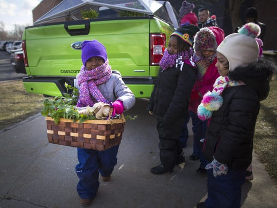A child carries produce and plants from a special F-150 at a local Detroit school as the children get hands-on lessons about farming as part of the Ford Mobile Farm.