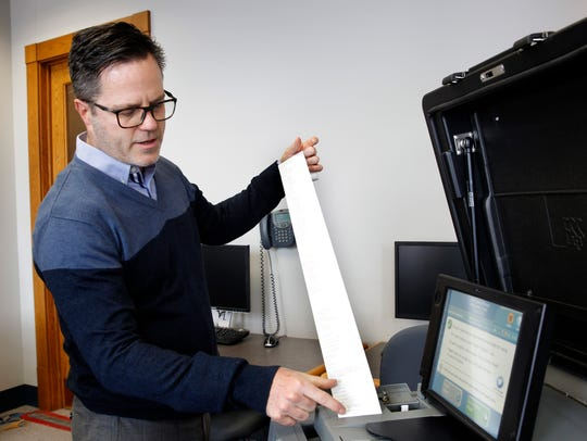 Neil Albrecht, executive director of the Milwaukee Election Commission, examines a paper tape record produced by one of the city's electronic voting tabulators. This was during a public test of the equipment Tuesday in anticipation of next week's election.