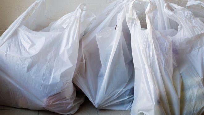 Plastic shopping bags on tiled floor.