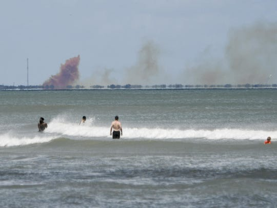 A cloud of orange smoke rises over nearby Cape Canaveral