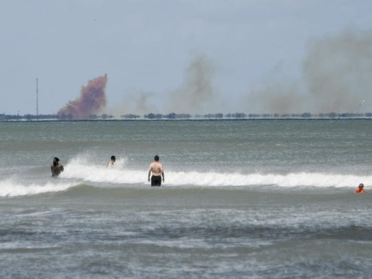 A cloud of orange smoke rises over nearby Cape Canaveral Air Force Station as seen from Cocoa Beach, Fla., Saturday, April 20, 2019. SpaceX reported an anomaly during test firing of their Dragon 2 capsule at their LZ-1 landing site.