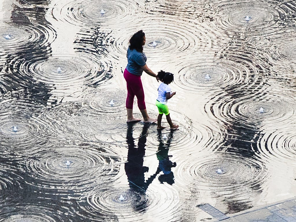 A woman and child walk through the cool water of a fountain on a warm spring afternoon at Dilworth Park in Philadelphia.