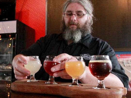 Keston Helfrich builds a beer flight in the Carolina Bauernhaus bar area.
