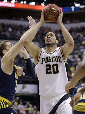Purdue Boilermakers center A.J. Hammons (20) shoots over Michigan Wolverines forward Mark Donnal (34) in the first half of their Big Ten tournament semifinal game Saturday at Bankers Life Fieldhouse.