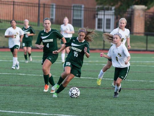 Parkside's Kara Osborne (15) moves the ball around Queen Anne's Shannon Donovan (6).