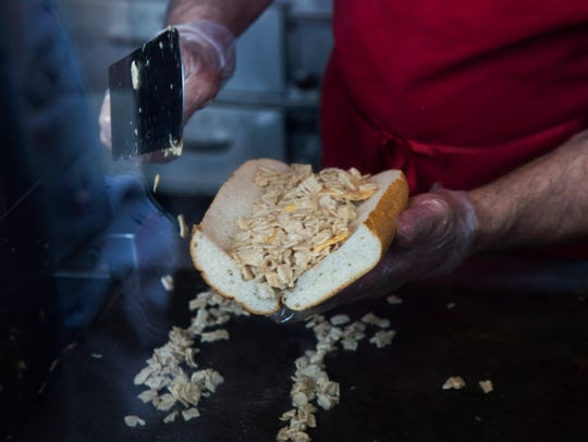 Aramark cook Frank Raggio prepares a vegetarian cheesesteak