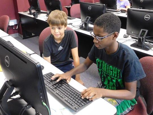 Campers work collaboratively on coding projects, embedding