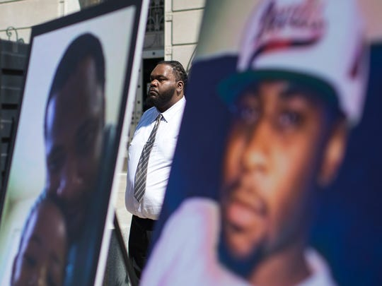 Vincent Osby, stepfather to murder victim Christian Phillip Nolan Rodgers, stands behind photos of his stepson during a press conference Monday, July 31, 2017 in Trenton.